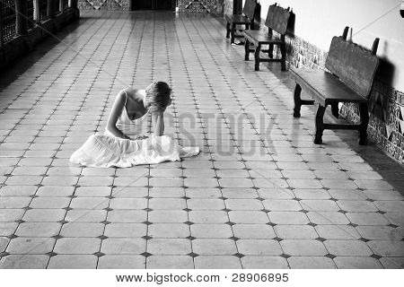 Young woman in white dress on the floor