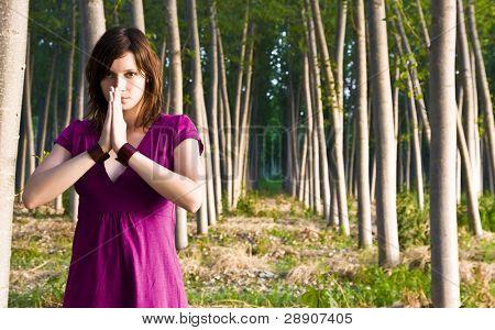 Jovem mulher praticando ioga em uma floresta.