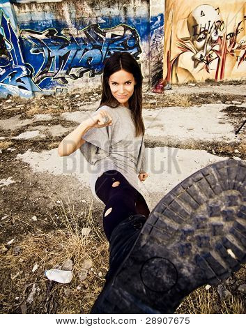 Young rebel woman kicking in dirty urban background. Focus on face.
