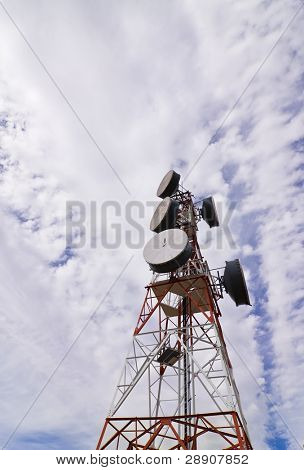 Telecommunication antenna under clouded sky.