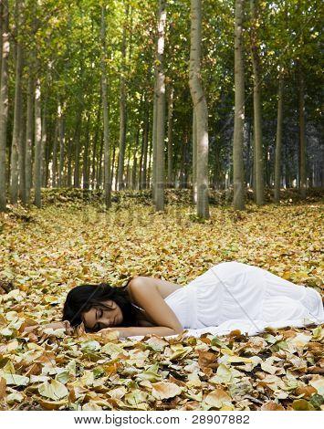 Beautiful woman sleeping over fallen leaves.