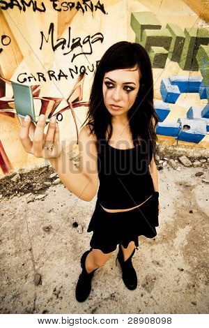 Goth girl looking mirror in urban background.
