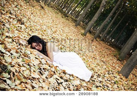 Beautiful woman sleeping over fallen leaves.