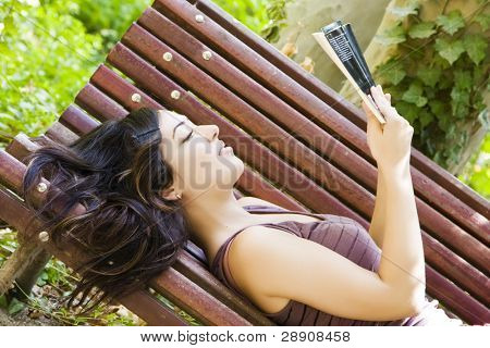 Reading woman laying in a park bench.