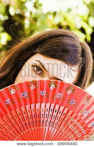 Mujer española detrás de ventilador tradicional.