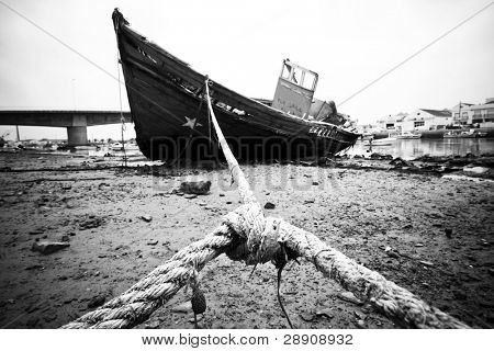 Abandoned wooden ship, still strapped.