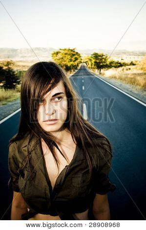 Young girl who seems confused in an empty road.