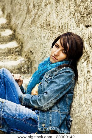 Young thoughtful woman sitting on stone stairs.