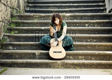 Young beautiful music performer caressing her guitar