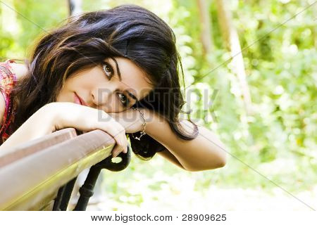 Young beautiful dreamer in a park bench
