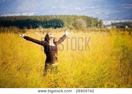 Woman feeling freedom surrounded by autumn colors.