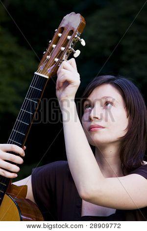 Young performer adjusting her hispanic guitar.