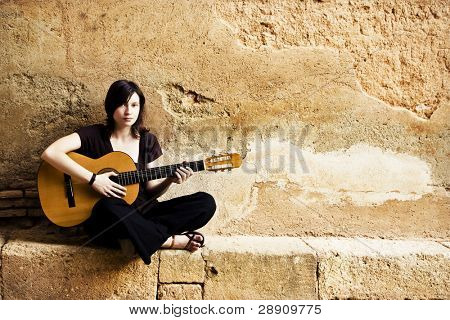 Young female guitar performer posing with her instrument.