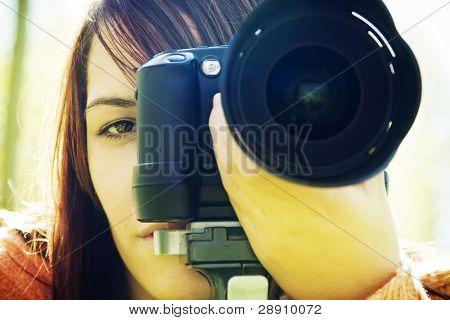Young woman eye behind slr camera.