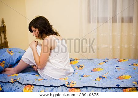 Tormented young woman in her bedroom