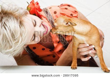 Jovem beleza loira brincando com seu animal de estimação.