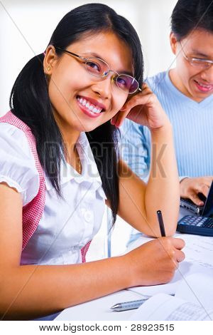 Female scholar smiling to the camera while the male scholar on the background typing on his laptop