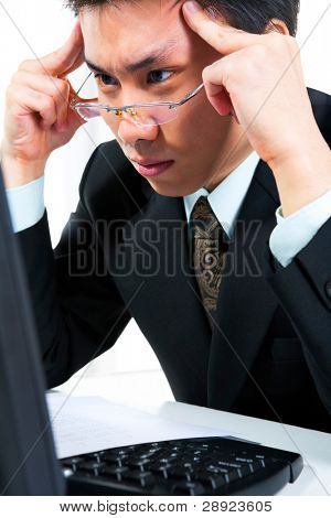 Side view of a young businessman thinking very hard in front of his computer in office.