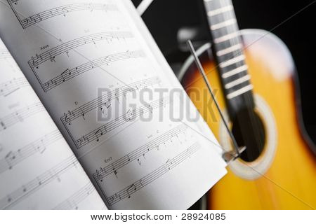 Musical chords and guitar on background in dark