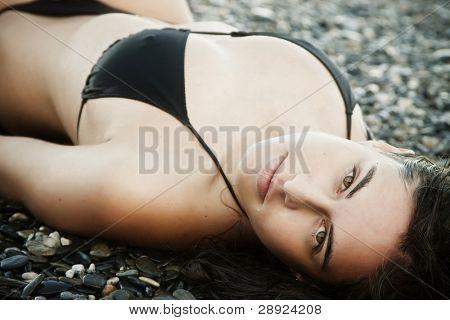 Laying beauty wearing black small bikini.