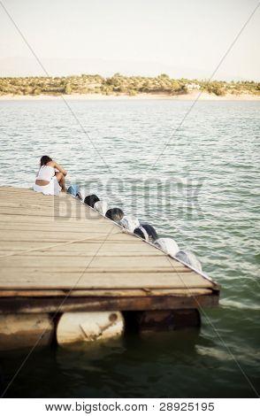 Junge Frau sitzt auf dem Pier. sehr flach Dof. Das Mädchen im Mittelpunkt.