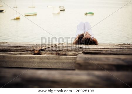 Young pensive woman over wooden surface near the water