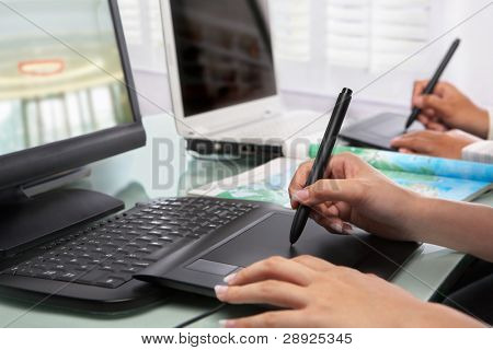 Graphic designers working in office with no face recognizable here. PS: selective focus on digital pen