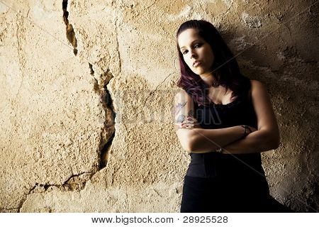Young beautiful redhead woman portrait on cracked wall.
