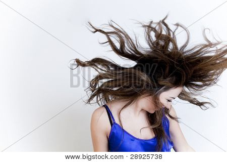 Young beautiful girl with windy hair over white background.