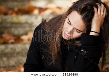 Young beautiful thoughtful girl in autumn background