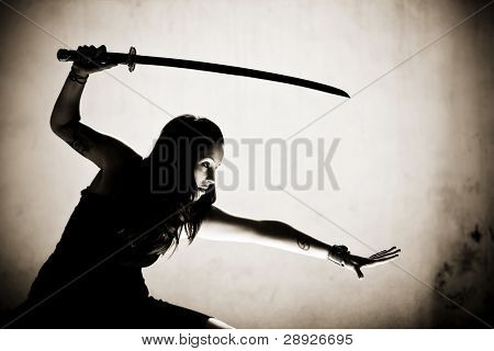 Female gothic warrior posing with katana sword.