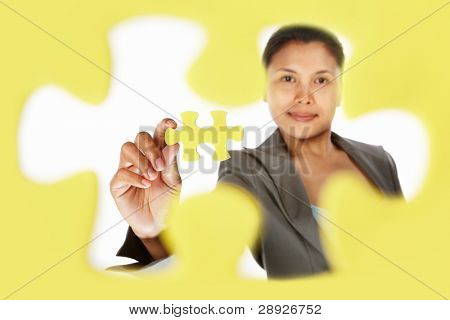 Asian businesswoman showing the last piece of puzzle, over white background