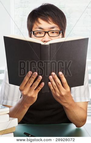 Chinese college male student holding up his book high