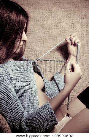 Young beautiful woman undoing her cardigan.