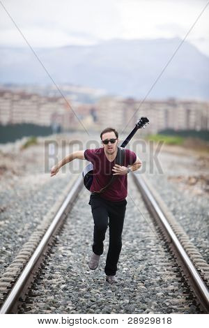 Young male musician running on railway road.