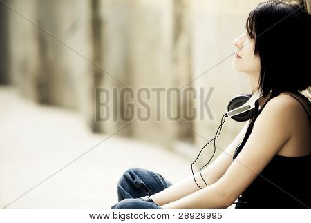 Young pensive beautiful woman sitting with headphones on her neck