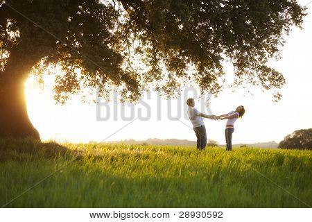 Young playful couple under huge tree at sunset