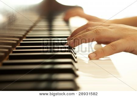 Hands over piano in warm tones.