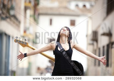 Young beautiful guitarist in urban background.