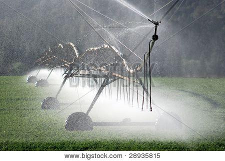 Modern irrigation pivot watering a farm field