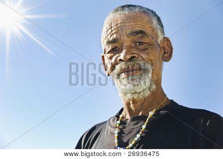 Senior African man against blue sky