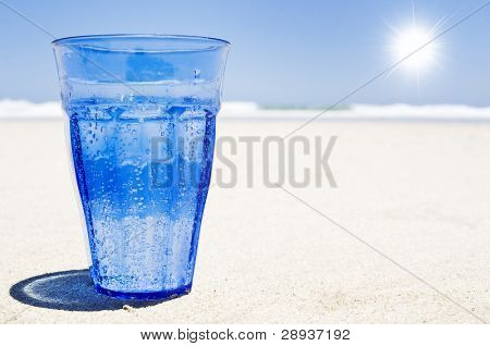 a Glass of sparkling water on a clean beach with sun and sky