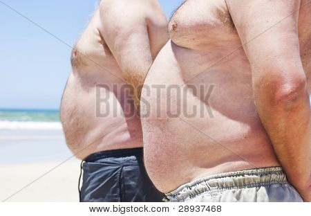 Two fat men showing their bellies on the beach