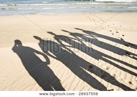 The silhouettes of five people on the beach