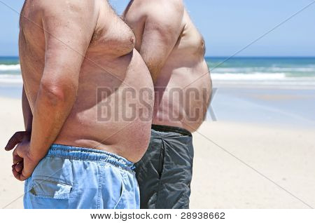 Close up of two fat men showing their bellies on the beach