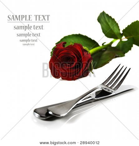 a Beautiful red  rose with a setting with knife and fork on a pure white background with space for text