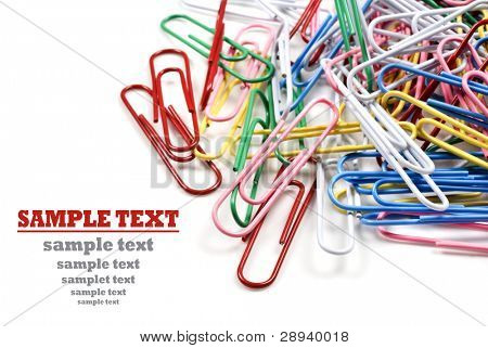 Colourful paper clips on a white background with space for text