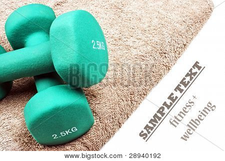 a Pair of green dumbbells on a towel with space for text on a pure white background