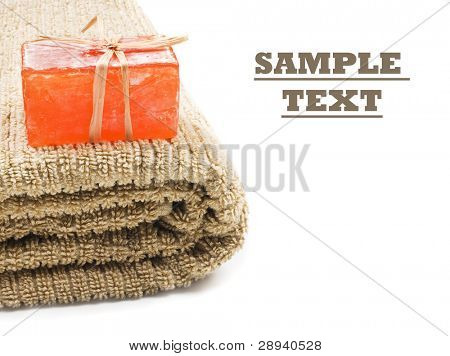 a Bar of homemade soap on a clean folded towel - close up on a white background with space for text