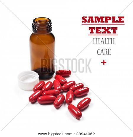 Red pills spilled around a brown pill bottle on a pure white background with space for text